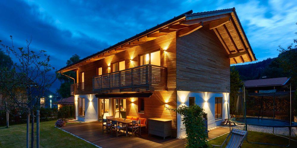 Seitenansicht des Einfamilienhauses von Stadler Bau am Schliersee bei Nacht